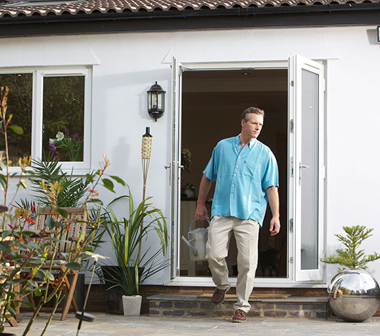 Man standing outside his patio doors in a blue shirt carrying a watering can