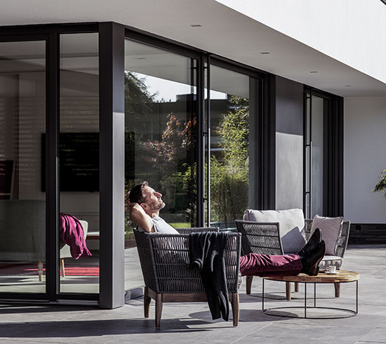 Man relaxing in the sun in a chair by his black windows and doors